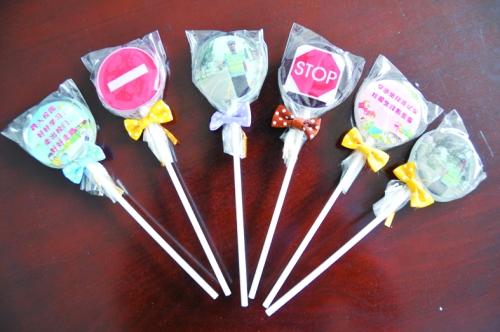 把交通安全标识做成棒棒糖,送给幼儿园的小朋友,以这种特殊的方式让小